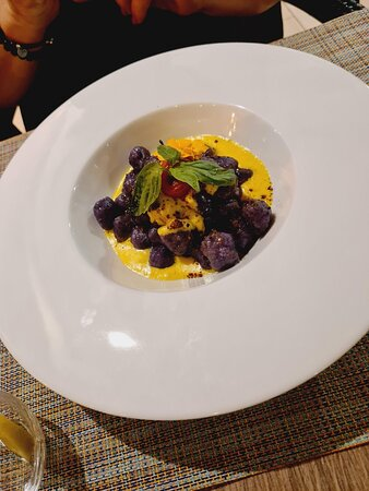 Joquis de patata violeta con crema de gorgonzola, azafrán y pistachos