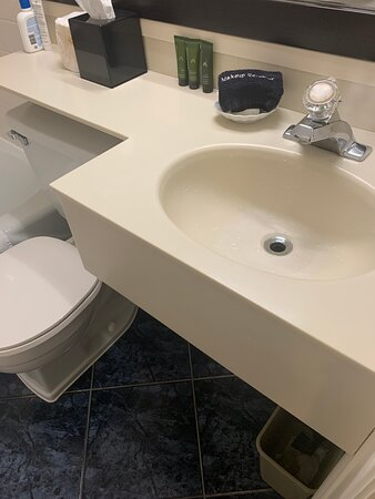 Tiny bathroom, linoleum floor, no storage, dated fixtures
