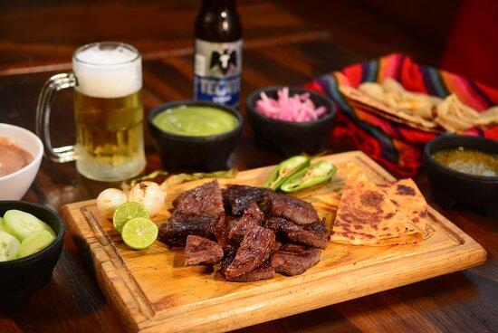 Carne cecina estilo Obregón, el sabor de Sonora se encuentra en esta carne oreada al sol y asada a la parrilla. Se acompaña con frijoles puercos, quesadillas, guacamole, salsa y tortillas.