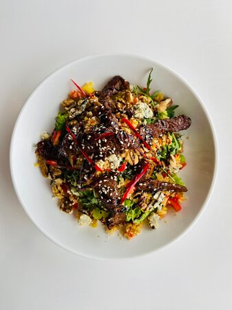 Steak Salad, In a sweet chilli and soya sauce, topped with sesame seeds on a bed of mixed salad.