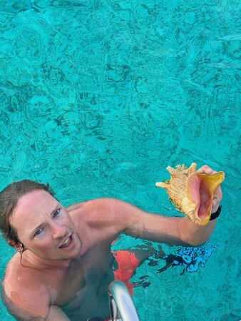 Captain Pieter surfaces with a conch.