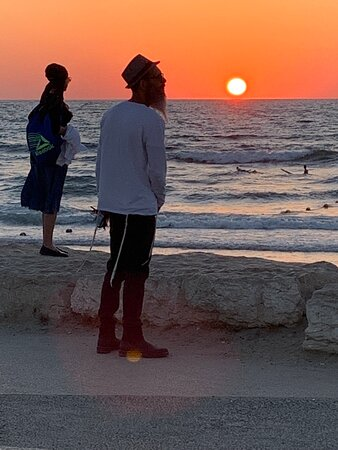 """Ten great photos of sunset from this attraction, as our friend pictured here, Bawmeh Gardney sings """"tomorrow may rain so I'll follow the sun.""""  Later, our good friend, Jorjah Risson, joined and sang """"here comes the sun""""- it was way too early for that, but """"I say, it's alright."""""""