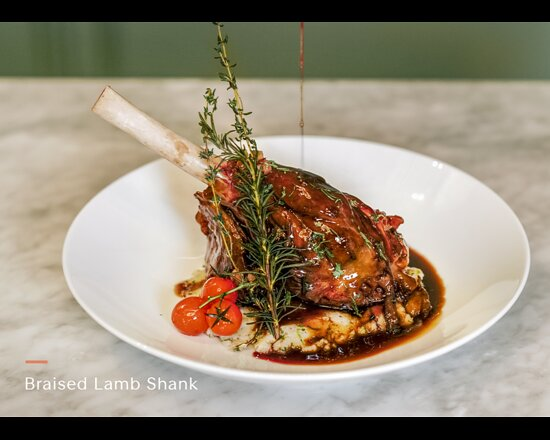 Slow cooked lamb shank served with roasted potato and pear topped with mint and pear gravy