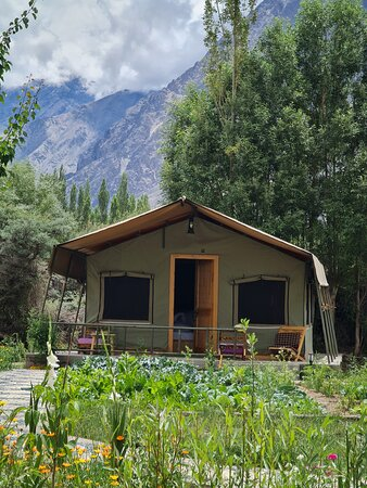 Lush green area, away from the hustle and bustle of the city. Surrounded by lofty snow clad mountains. The only sound you will hear is the gently blowing breeze and the gurgle of the rivulet