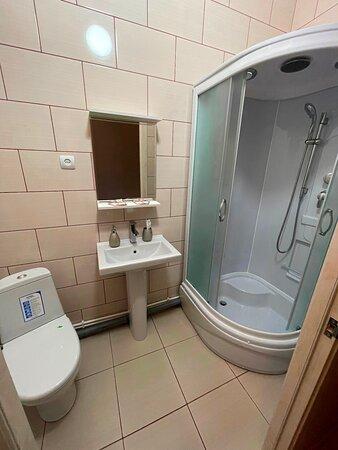 """Khadyzhensk, Nga: Номера """"Комфорт""""  рассчитаны на проживание двух человек. Состоят из односпальных кроватей. Номер оборудованы телевизором, кондиционером, холодильником, чайником, феном. Имеется шкаф, стол со стульями.  По вашему пожеланию предоставляется сейф.  Санузел отдельный, оснащен туалетными принадлежностями, находится в номере.  Стоимость проживания: 1700 ₽/номер"""