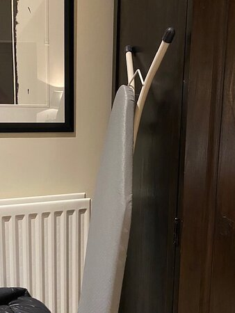 Ironing board propped up against the wardrobe which we would not expect to see in a hotel of this standard.