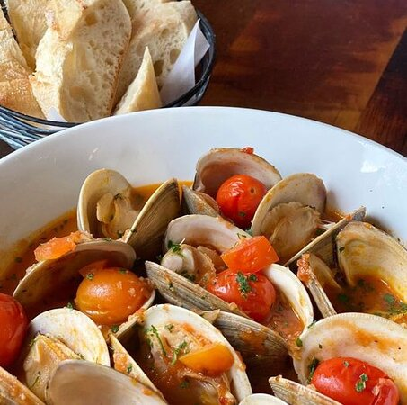 Calabrian Chili Clams  Local Middleneck clams in a white wine and tomato broth with Calabrian chilis, fennel and roasted tomatoes. Served with a toasted baguette