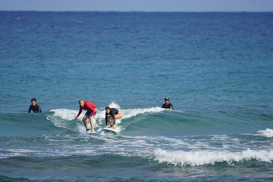 My daughter and I catch the same wave while Dom and his partner look on in amusement at our predicament.
