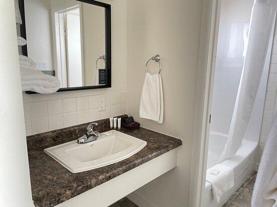 Salle de bain étroite, le comptoir vanité est séparé de la douche et la toilette