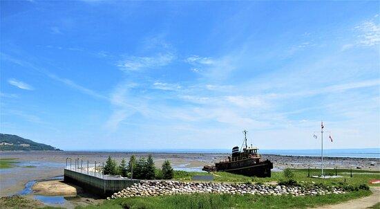 """Le musée maritime de Charlevoix, le remorqueur Félicia et le quai où nous pouvons apercevoir l'épave du """"Mont Ste-Marie"""", incendiée en 1998"""