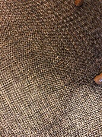 Food crumbs on carpet under table