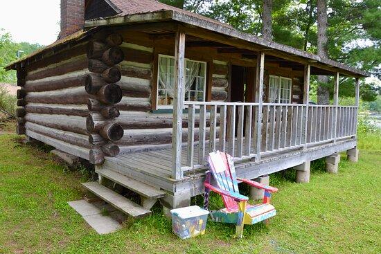 Log cabin and colourful Muskoka chair