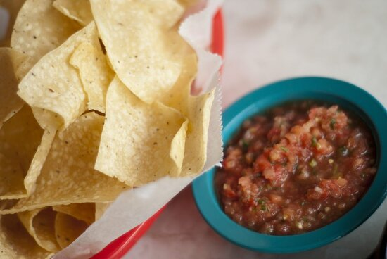 Chips are fried in-house and served with Salsa Fresca, made in small batches with fresh tomatoes, serrano peppers, and onions.