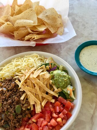 Taco Salad - fresh salad mix topped with cheese, guacamole, tomatoes, seasoned ground beef and crispy tortilla strips for extra crunch. Try it with Creamy Jalapeño as your dressings.