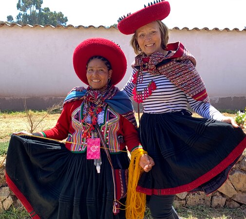 """Mama Sherpa surprised us by playing """"dress up"""" with traditional Peruvian clothing.  Check out the fresh fuchsia necklaces!  Such fun!"""