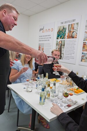 Anno's experiences host pours Berry Pink Gin into a visitors' glass during a tour and tasting at the distillery.