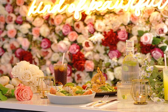 Grilled salmon nicoise with sea food salad on a marble table, with a flower wall background at #fioredellamore #fioredellamoreuk