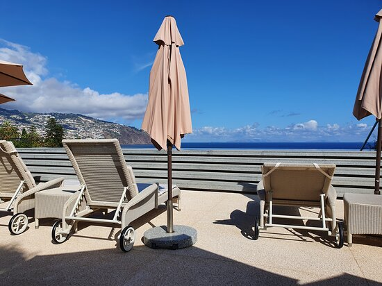 Les Suites Infinity Pool deck chairs looking out over the Funchal Bay.