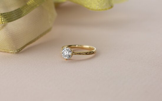 This unique vintage engagement ring features a round-cut diamond and beautiful filigree detailing