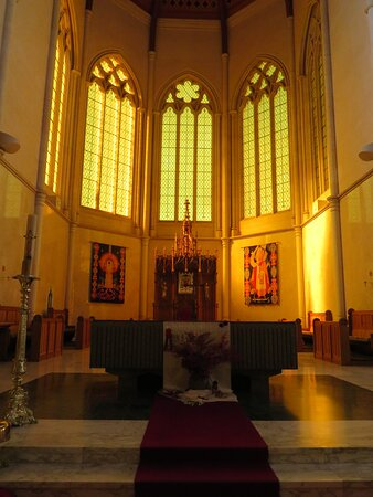 Chancel at the eastern end of the cathedral. It ends in a semi-circular sanctuary in the apse. Five clear-glass windows. Step up to the altar. Evening time and growing dark.