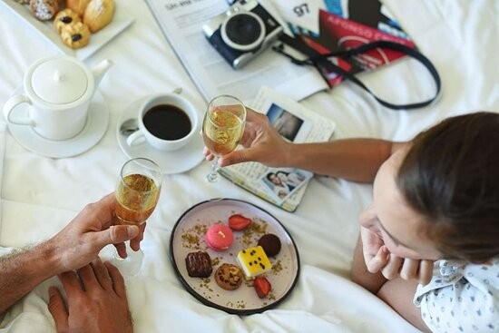 Guests Eating and Drinking Champagne in Bed