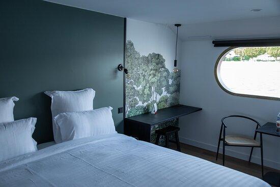 La nature est omniprésente, elle s'invite jusque dans cette chambre avec ce papier peint représentant une forêt luxuriante sous un ciel clair. On a envie de se laisser aller à une rêverie contemplative en observant les moindres détails de ce dessin. Un joli moment de slow life en perspective...