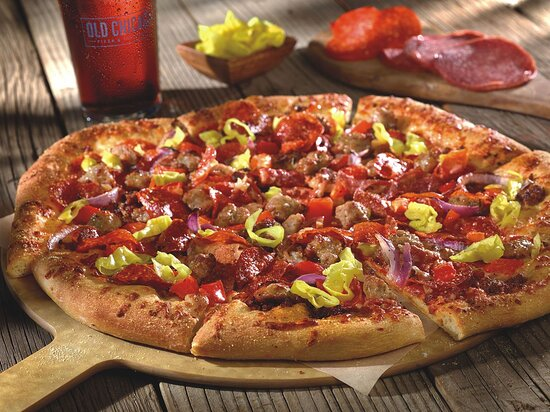 ITALIAN GRINDER PIZZA  A classic combination of seasoned beef, salami, pepperoni, sweet Italian sausage, red onions, roasted garlic, red peppers and pizza sauce, finished with sliced pepperoncini.