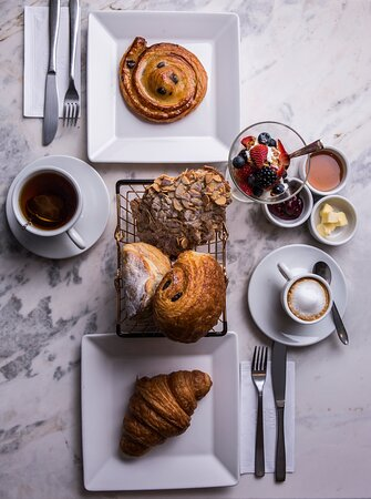 Café da manhã completo! Com café, iogurte, croissant e doces.
