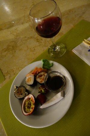 Суши, фрукты и вино из азиатского ресторана.