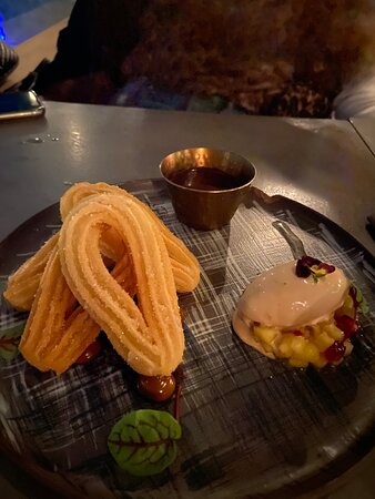 Crispy, dry churros with weird ice cream, tiny dots of dulce de leche and lovely dark chocolate sauce