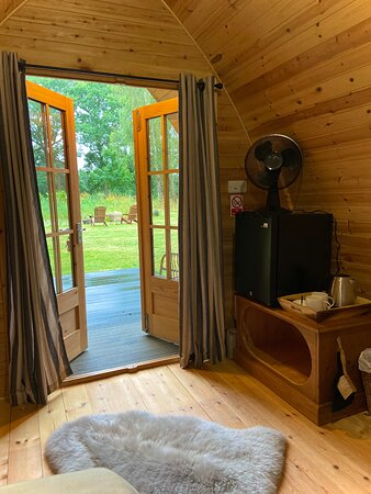 Inside Sleepy Hollow, two berth pod at Bluebell Retreat Glamping.  Two hotel quality single beds (can be made into double) sit facing the wooden double doors with beautiful views of the meadow and pond.