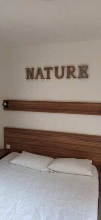 Tête de lit (avec le mot NATURE pour tout décor)