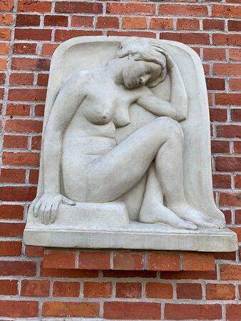 Рельеф «Гениус» или «Сидящая на корточках девушка» установлен на стене Пакгауза со двора