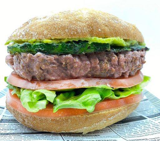 Burger Nueva delhi, burger vegana con lechuga, tomate, calabacín, acompañada de una salsa de aguacate.