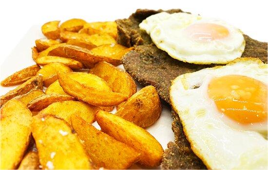 Ternera rebozada con huevo fritos y patatas gajos de luxe especiadas.