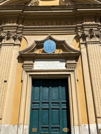 There is a single entrance, with a large doorcase. Above this is a marble tablet with a long dedicatory inscription, flanked by a pair of entablature fragments with globular tassels. Above this in turn is a rather fantastic pentagonal pediment with incurved sides -a Borrominian detail. The tympanum of this is now blank, but looks as if it once contained something.