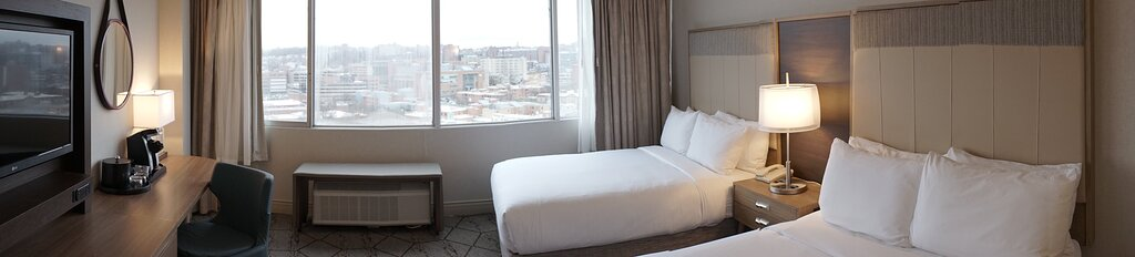 Renovated room with two beds, overlooking Syracuse.