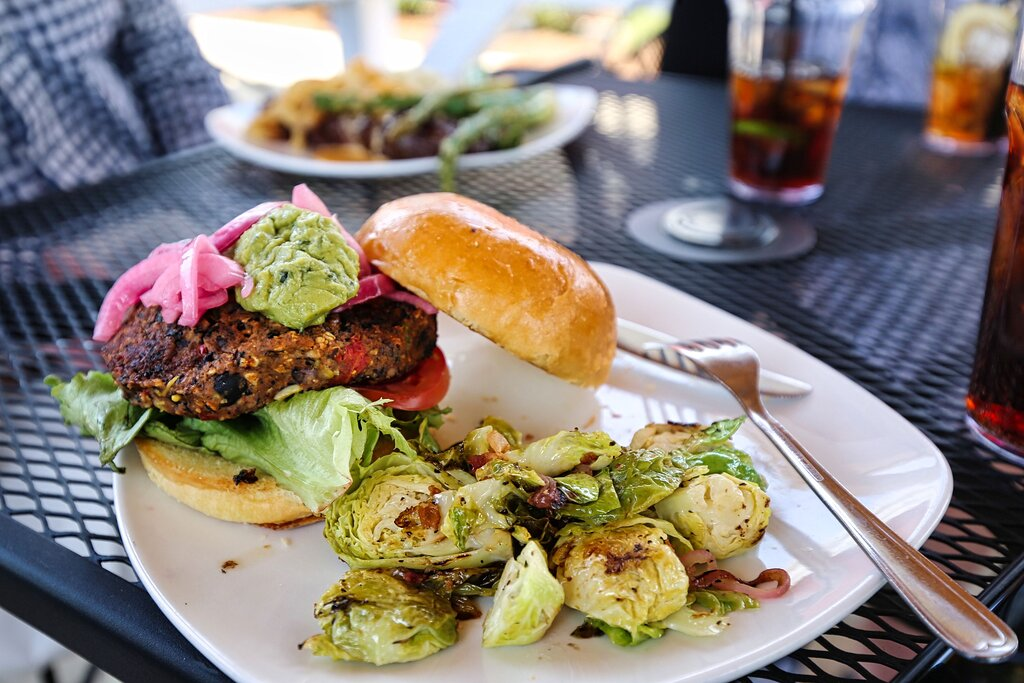 Black Bean Burger - A zesty grilled black bean burger topped with guacamole, crisp greens, tomatoes, pickled red onions and served with your choice of side.