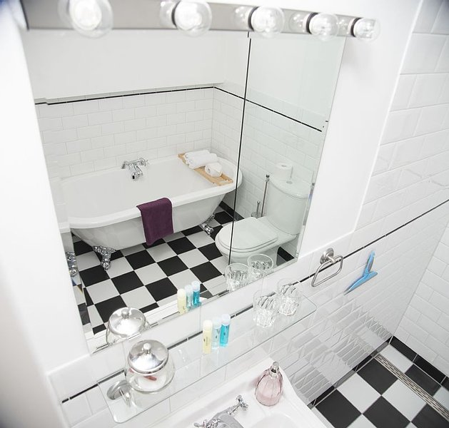 Two identical bathrooms, with rain shower and freestanding bathtub