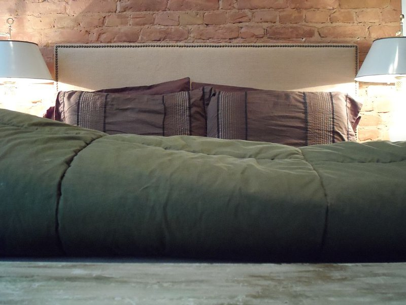 Full sized American bed and exposed brick walls.