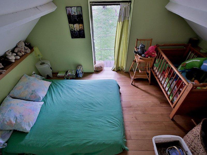 La chambre N°5 à l'étage avec lit de bébé.