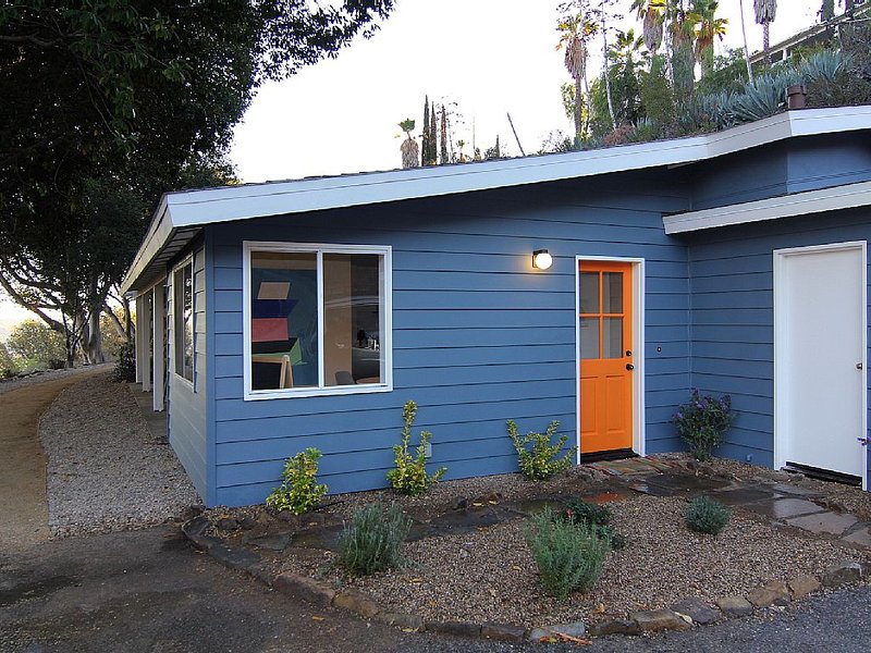 Welcomed from the carport by the bright orange door