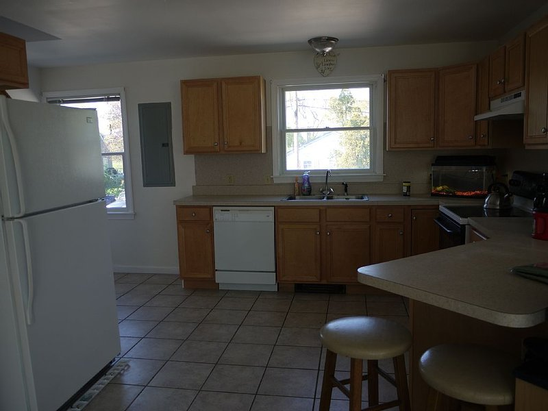 large spacious kitchen with utensils, pans, etc.