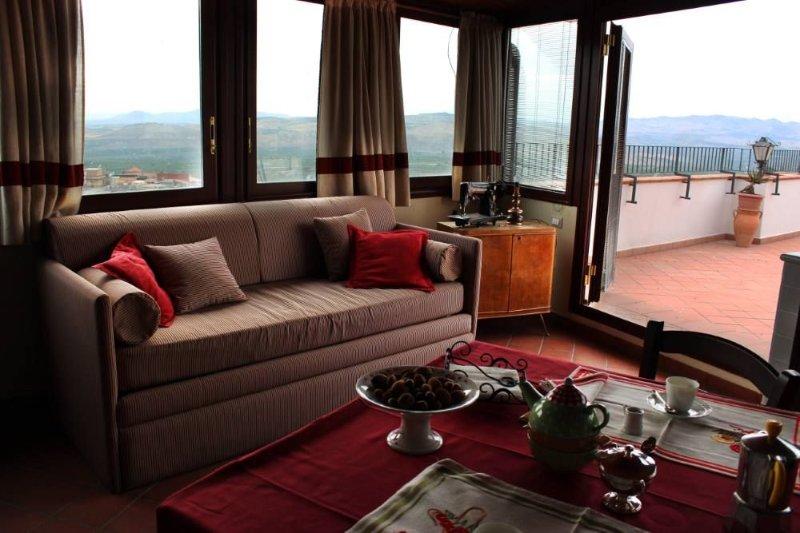 Interno salotto con vetrate affacciate alla collina storica, con divano-letto