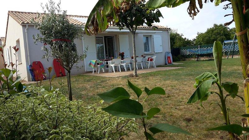 La maison, la terrasse sous le store banne et le jardin d'agrément