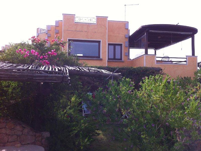 Vista esterna della casa con le terrazze coperte e il giardino