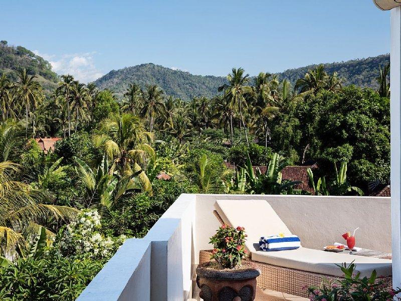 Beautiful lush palm tree and mountain views from the wraparound Joglo verandah