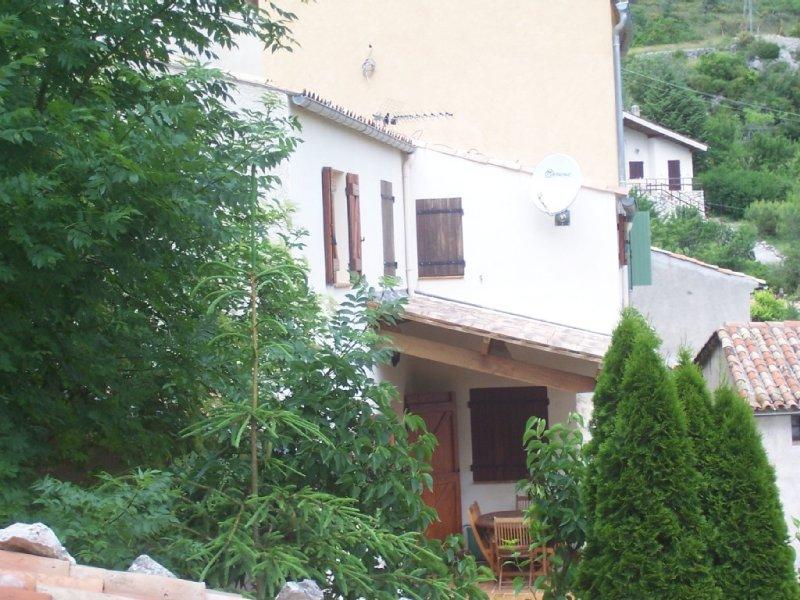 Entrée par la terrasse dont une partie est protégée par un auvent.Agréable lieu