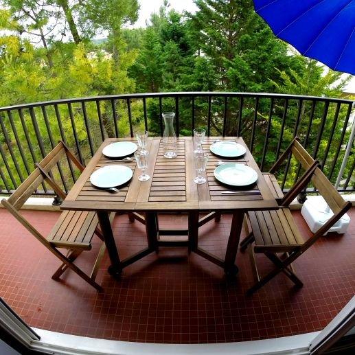 Grand balcon avec une vue dégagée. Meublé avec 1 table, 5 chaises, et 1 desserte