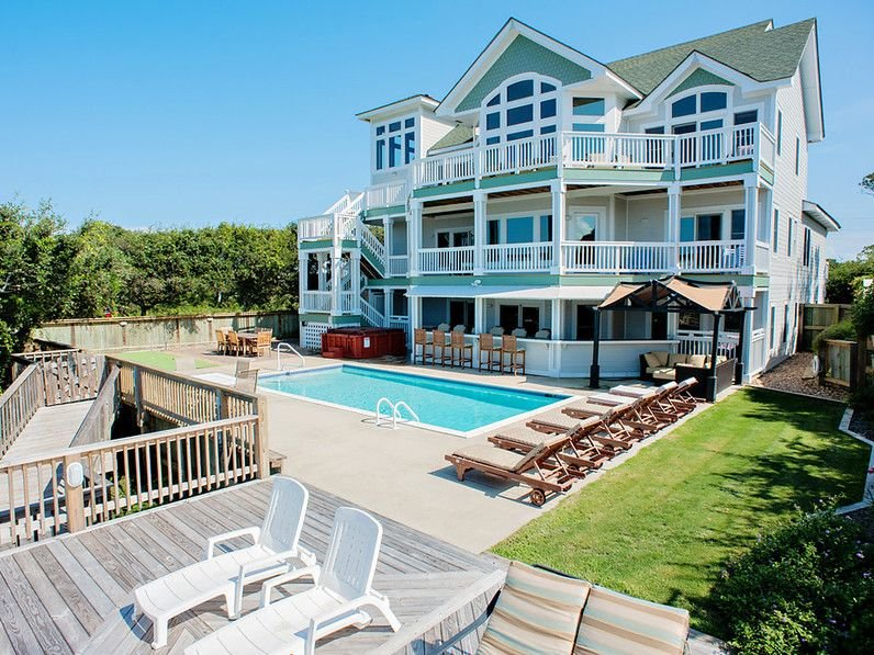 Expansive soundfront pool deck with hot tub and access to private sandy beach.